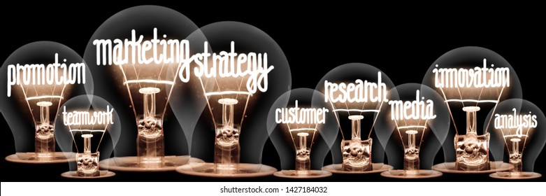 Photo of light bulbs with shining fibers in shapes of Marketing Strategy concept related words isolated on black background