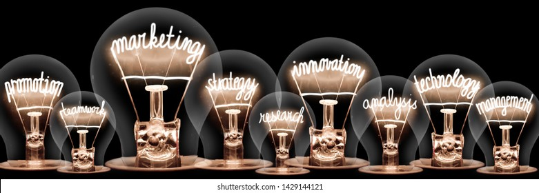 Photo of light bulbs with shining fibers in shapes of Marketing, Innovation, Technology and Strategy concept related words isolated on black background