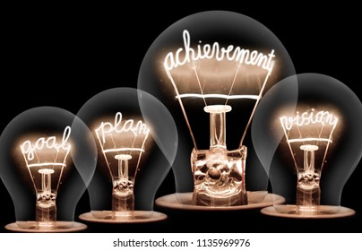 Photo of light bulbs with shining fibres in ACHIEVEMENT, GOAL, PLAN and VISION shape on black background