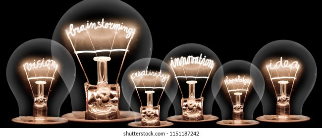 Photo of light bulbs with shining fibres in BRAINSTORMING, IDEA, VISION, INNOVATION, CREATIVITY and KNOWLEDGE shape on black background