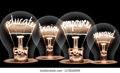 Photo of light bulbs with shining fibres in EDUCATE, TRAIN, EMPOWER and REWARD shape on black background