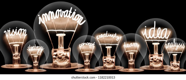 Photo of light bulbs with shining fibres in INNOVATION, IDEA, VISION, CONCEPT and CREATIVITY shape on black background