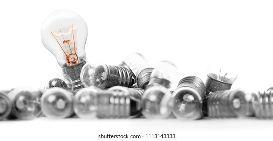 Photo of light bulbs with shining one on white background; concept of standing out, uniqueness and idea
