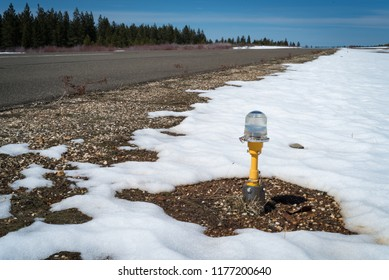 A photo of a light next to an airstrip at a small rural airport with a large snow patch around it.