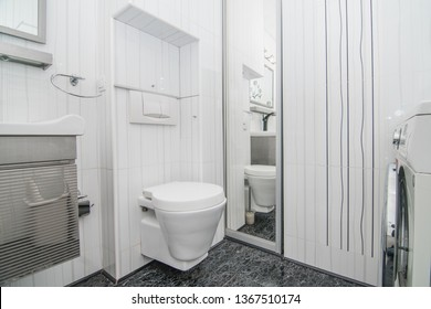 The photo of the light white bathroom with household appliances