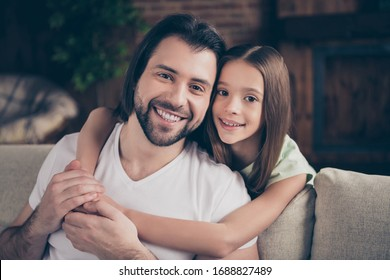 Photo of little adorable pretty lady her handsome young daddy sit comfy sofa hugging piggyback spend time feelings parenthood friendship domestic house room indoors