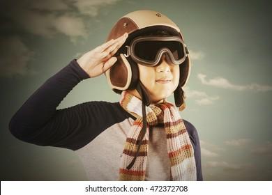 Photo of a little boy giving respectful gesture while wearing an aviator helmet, shot outdoors