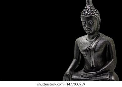 Photo of little buddha sitting from black stone isolated