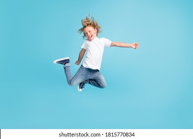 Photo of little child jump raise legs stick-out tongue wear white shirt jeans sneakers isolated blue color background