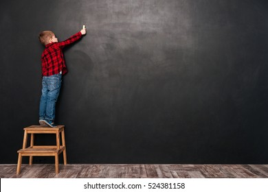 Photo of a little cute child standing on stool near blackboard and drawing on it.