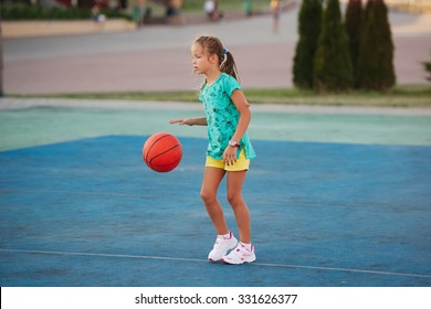 photo of little cute girl playing basketball outdoors