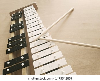 Photo of little cymbals. On a light table lies a cymbal instrument with chopsticks to extract sound from the plate.