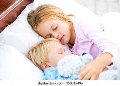 Photo of little girl and boy sleeping on white bed. Sister and brother hugging