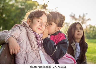 Photo of little girl sitting on a bench and whispering to her friend
