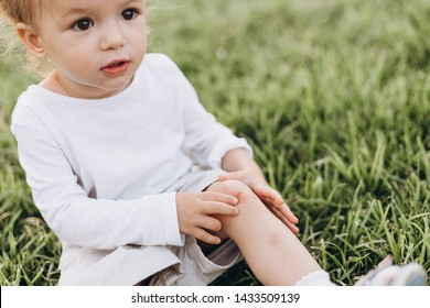 photo of a little girl who fell and scratched his knee in the blood, it hurts the wound and it keeps a handle on the leg, but not crying