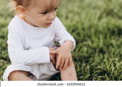 photo of a little girl who fell and scratched his knee in the blood, it hurts the wound and it keeps a handle on the leg, but not crying. the concept of a safe and fun childhood.