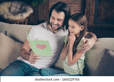 Photo of little pretty funny lady handsome daddy sitting cozy sofa hugging hold birthday card reading greeting words amazing wished relatives holiday house room indoors