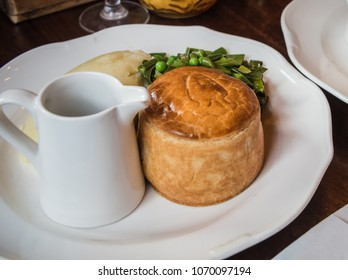 A photo of a London pub-style meat pastry pie with green vegetables, mashed potatoes and a cup of gravy.