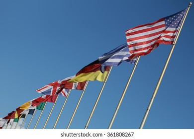 Photo long shot of different national flags flutter in wind on tall flagstaffs in rows against bright blue sky background, horizontal picture