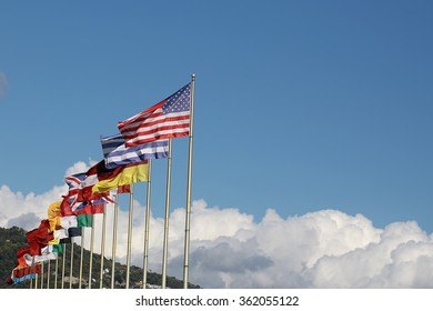 Photo long shot of row of different national flags flutter in wind on tall flagstaffs green mountains fluffy white clouds on blue sky background, horizontal picture