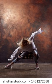 Photo of long-haired blonde in ripped jeans dancing on brown background