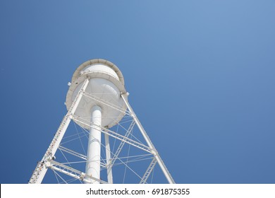 Photo looking up at a white water tower with a bright blue sky.