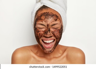 Photo of lovely delighted woman with pleased face expression, gets pleasure from beauty treatments, feels relaxed and satisfied, stands topless against white studio wall. Health care, natural beauty