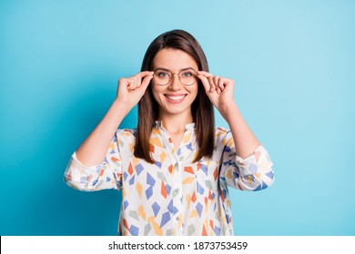 Photo of lovely girl hold eyewear beaming smiling look camera wear eyeglasses geometry print shirt isolated blue color background