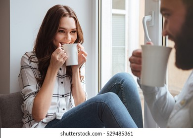 Photo of loving couple sitting together and drinking tea indoors near window.