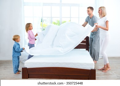 Photo of loving family of four making bed. Young family demonstrating quality of mattress and holding blanket