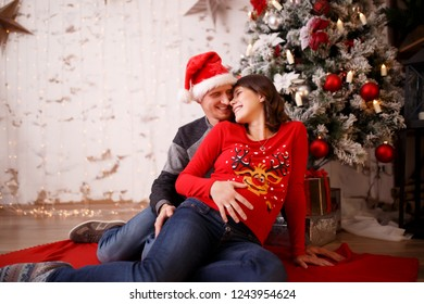 Photo of loving man and pregnant woman on background of Christmas decorations