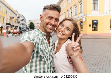 Photo of loving young couple in summer clothes smiling and showing peace sign while taking selfie photo on city street