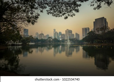 The photo of Lumpini park, Bangkok Thailand. This photo showing bangkok skyline over the lake in the park with stunning refection.