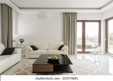 Photo of luxurious leather sofa and small wooden table