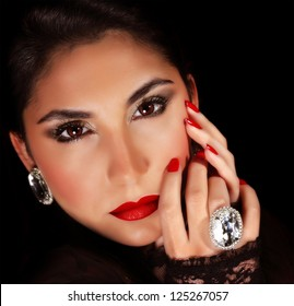 Photo of luxury female wearing stylish jewelery, closeup portrait of beautiful woman with seductive makeup isolated on black background, sexy girl, red lips, Valentine day, beauty and elegance concept