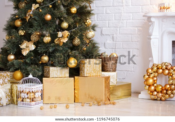 Photo of luxury gift boxes under Christmas tree, New Year home decorations, golden wrapping of Santa presents, festive tree decorated with garland, baubles, traditional celebration. Copy space