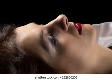 Photo of lying woman in profile on black background