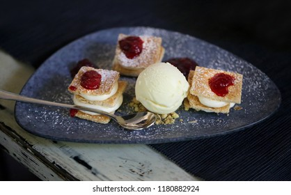 Photo of a macro delicious cake with cream in a restaurant on a dark plate