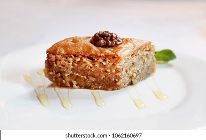Photo of macro sweet honey baklava on a white plate