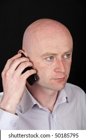 photo male in his 30's in shirt on black back drop holding a mobile phone to his head ear. eyes closeup and looking up. bald shaved head with hands on phone close to his head.