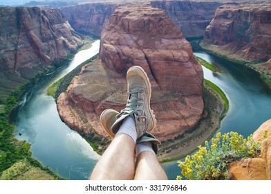 Photo of male legs in sneakers on the background of the canyon Horseshoe bend in Arizona. America.