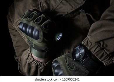 Photo of a male person in brown tactical outfit jacket and gloves using green tactical led flashlight and military watch.