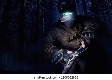 Photo of a male person in brown tactical outfit jacket, gloves and head flashlight using knife to clean out wood branches on night woods background.