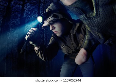 Photo of a male person in brown tactical outfit jacket and gloves walking in woods with head flashlight and tactical knife.