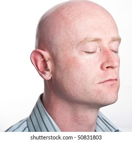photo male portrait close up on white backdrop. bald shaved businessman face closeup side profile eyes shut closed isolated on white. shaved bald man wearing a business type smart shirt.
