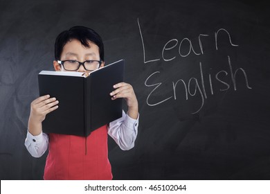 Photo of a male primary school student reading a book with text Learn English on the chalkboard, shot in the class