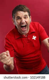Photo of a male Swiss sports fan wearing a Swiss flag shirt and screaming for his team.
