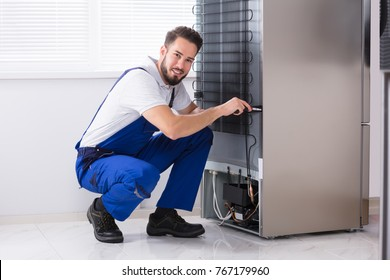 Photo Of Male Technician Fixing Refrigerator In Kitchen