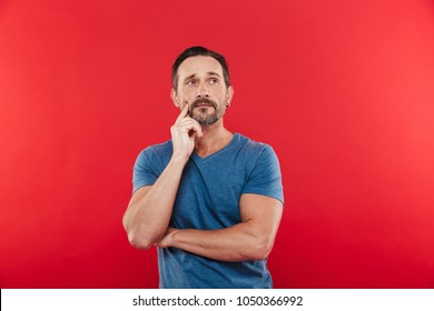 Photo of man 30s wih brooding gaze in casual t-shirt looking upward and thinking or remembering isolated over red background