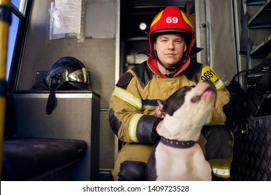 Photo of man fireman with lifeguard dog